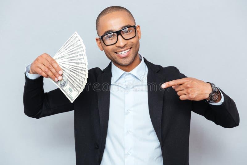 De gelukkige Afrikaanse dollars van de jonge mensenholding en het richten op het stock foto's