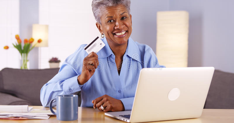 De gelukkige Afrikaanse oudste keurde met nieuwe creditcard goed stock foto