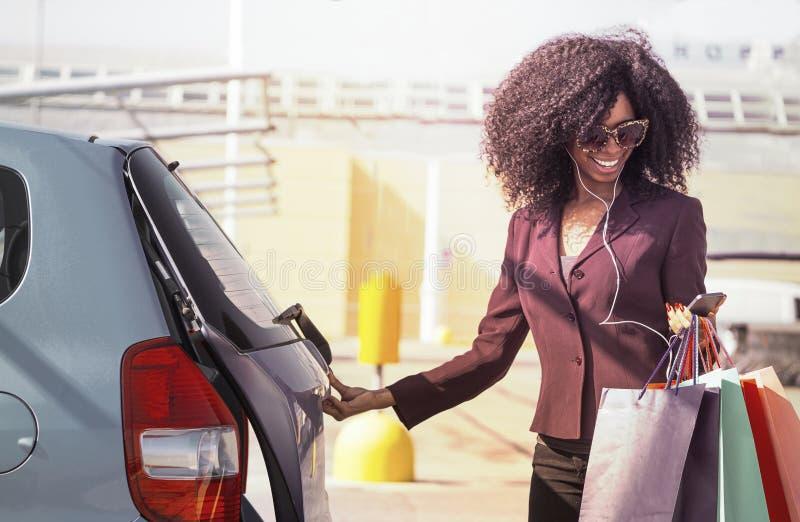 de gelukkige Afrikaanse vrouw met het winkelen doet het openen auto in zakken en het texting op mobiele telefoon stock fotografie