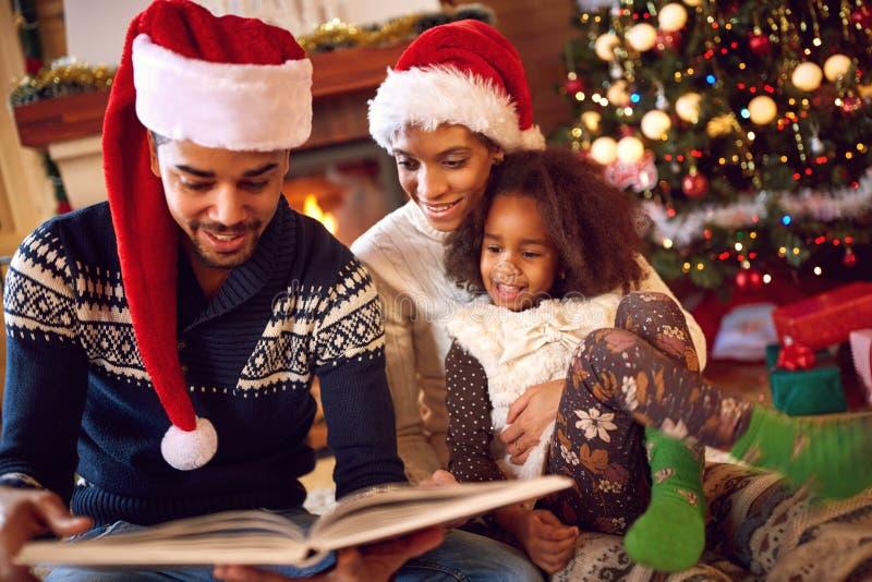 De gelukkige afro Amerikaanse familie las een boek bij open haard op Kerstmis stock afbeelding