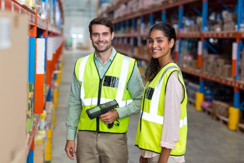 De gelukkige arbeiders glimlachen en stellen tijdens het werk stock fotografie