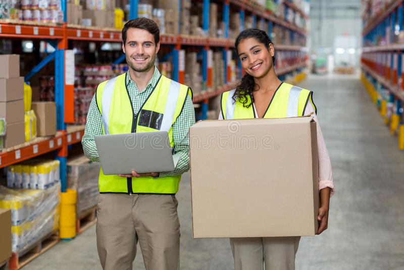 De gelukkige arbeiders houden laptop en karton doos en het stellen royalty-vrije stock fotografie