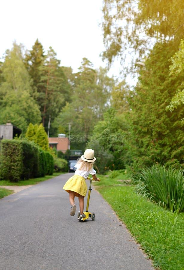 De gelukkige autoped van de het overhemds berijdende schop van de meisje gele rok witte openlucht, dragend roze veiligheidshelm royalty-vrije stock foto's
