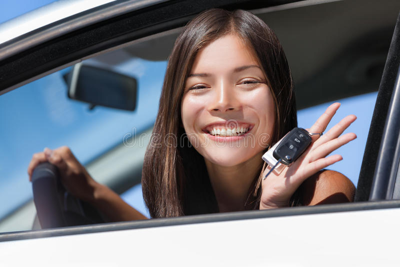 De gelukkige Aziatische bestuurder die van de meisjestiener nieuwe autosleutels tonen stock foto