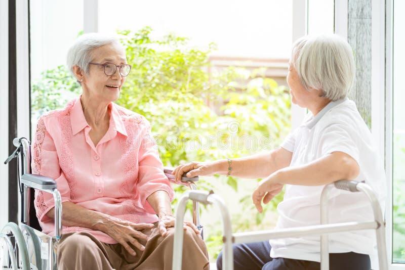 De gelukkige Aziatische hogere vrouwenzitting op rolstoel, zuster of vriend met leurder die pret, vriendschappelijke, vrouwelijke stock afbeeldingen