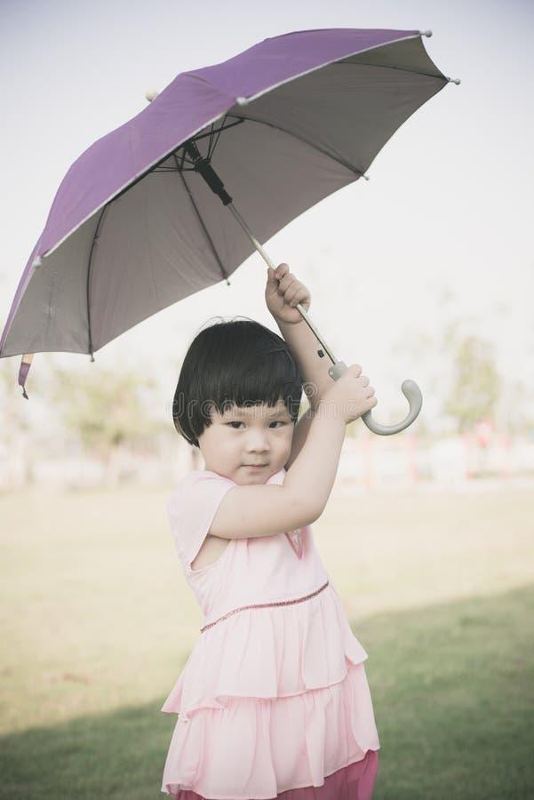 De gelukkige Aziatische paraplu van de meisjesholding openlucht stock foto's