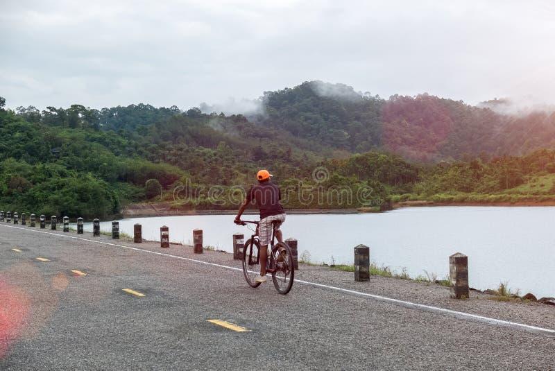 De gelukkige Aziatische Personenvervoerfiets op Landelijke Weg kijkt aan Aard Klaar om Vakantie te beginnen gaat Avonturenreis, o royalty-vrije stock foto's