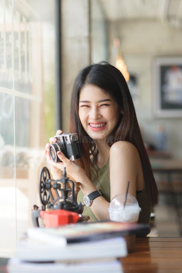 De gelukkige Aziatische uitstekende camera van de vrouwenholding in koffie, conc levensstijl stock afbeeldingen