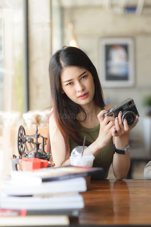 De gelukkige Aziatische uitstekende camera van de vrouwenholding in koffie, conc levensstijl stock fotografie