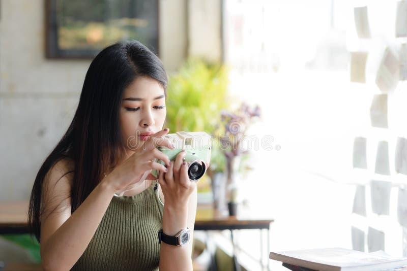De gelukkige Aziatische uitstekende camera van de vrouwenholding in koffie, conc levensstijl royalty-vrije stock afbeelding