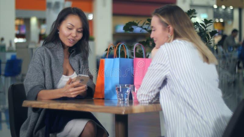 De gelukkige Aziatische vrouw die een nieuwe kleding bekijken, haar blonde vriend neemt foto van haar in winkelcomplex royalty-vrije stock foto's