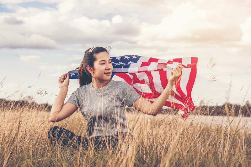 De gelukkige Aziatische vrouw met Amerikaanse vlag de V.S. viert 4 van Juli royalty-vrije stock afbeeldingen