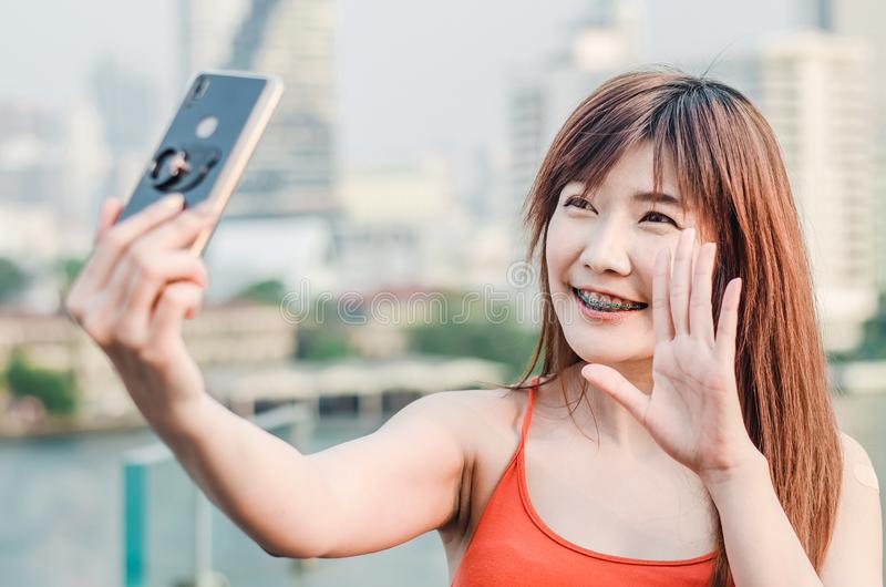 De gelukkige Aziatische vrouw met selfie of videogesprek hebben en telefoon die overhandigt stad golven nemen royalty-vrije stock foto