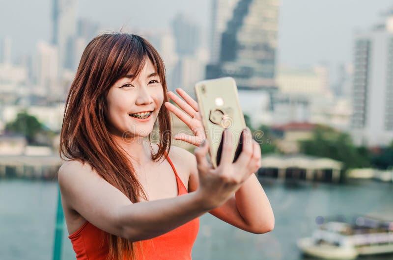 De gelukkige Aziatische vrouw met selfie of videogesprek hebben en telefoon die overhandigt stad golven nemen royalty-vrije stock afbeeldingen