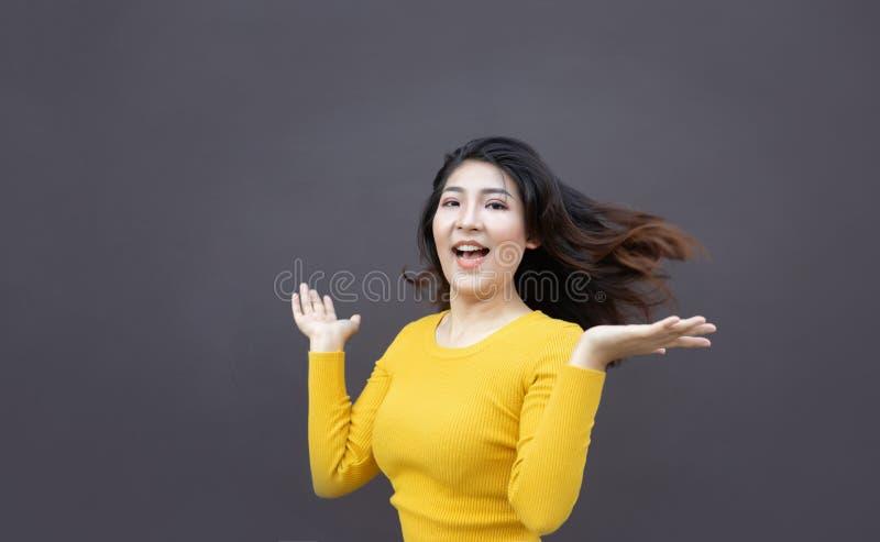 de gelukkige Aziatische de vrouwen open hand en glimlach tonen lang haar stock foto