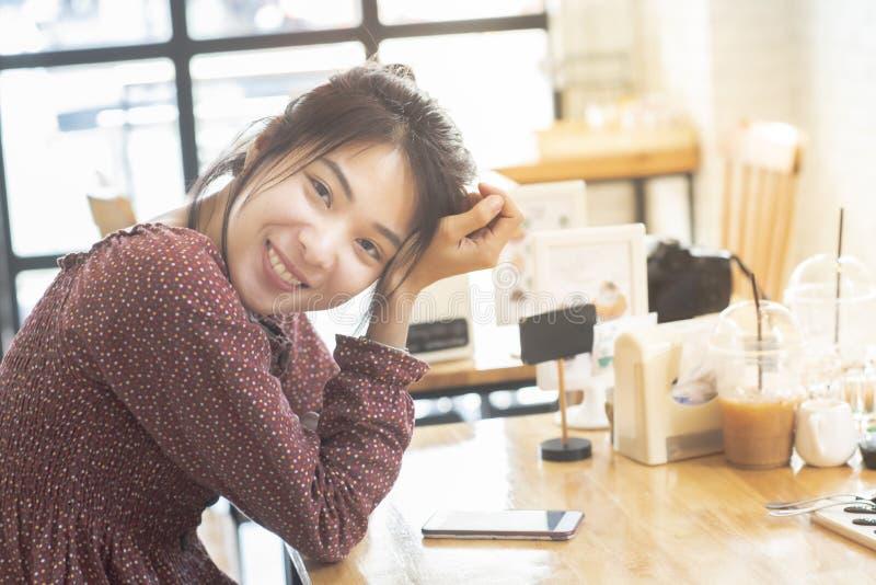 De gelukkige Aziatische vrouwentiener in toevallig kledingsgezicht bekijkt camera met grote glimlach zit op lijst in koffiewinkel stock foto