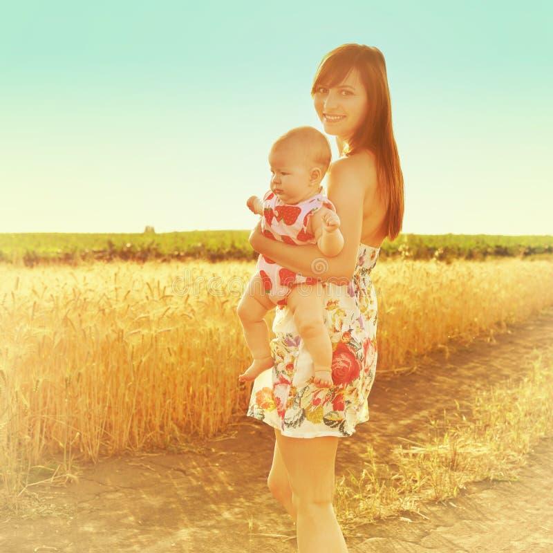 De gelukkige baby die van de moederholding op een tarwegebied glimlachen in zonlicht Mistig dalingseiland Portret van mamma en ba royalty-vrije stock foto's