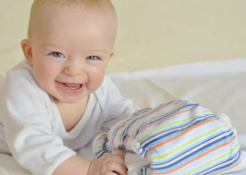 De gelukkige baby houdt doekluier stock afbeeldingen