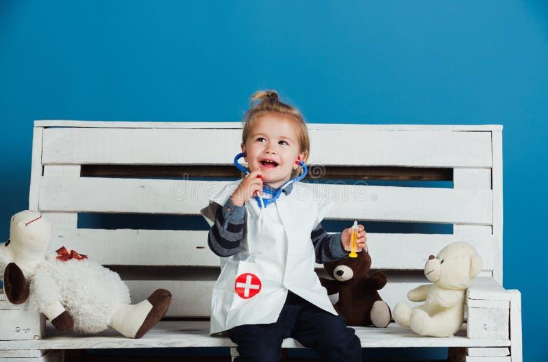 De gelukkige baby met stuk speelgoed huisdieren zit op houten bank stock fotografie