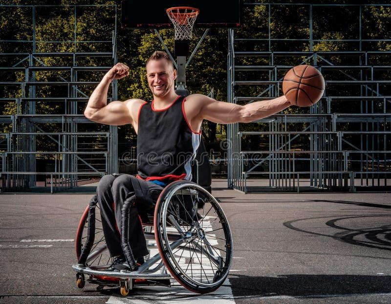 De gelukkige basketbalspeler in rolstoel stelt met een bal op open gokkengrond stock foto's