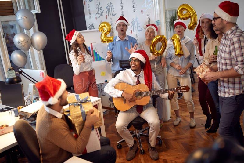 De gelukkige bedrijfsarbeiders hebben pret en het dansen in Kerstmanhoed bij Kerstmispartij royalty-vrije stock foto's