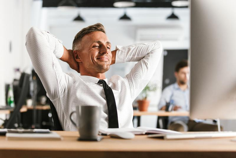 De gelukkige bedrijfsmensenzitting in bureau die met computer werken heeft een rust stock fotografie