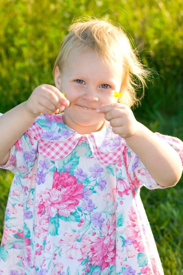 De gelukkige bloemen van de peuterholding in de zonneschijn. royalty-vrije stock afbeeldingen