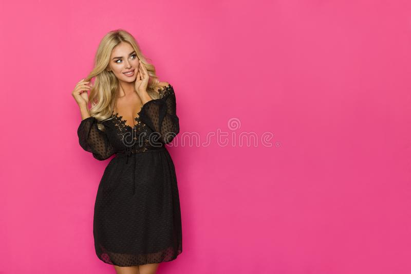 De gelukkige Blonde Vrouw in Zwarte Kantkleding bekijkt aan de Kant Roze Exemplaarruimte royalty-vrije stock afbeeldingen