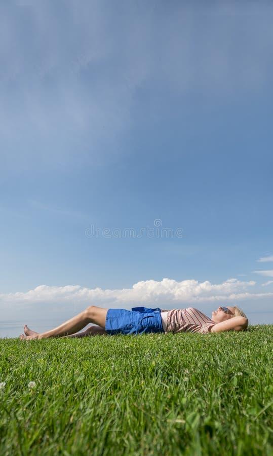 De gelukkige blootvoetse vrouw ligt op het groene gras, verheugt zich in de hitte en de zomer royalty-vrije stock afbeeldingen