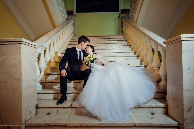 De gelukkige bruid en de bruidegom zitten op een witte marmeren trap, houden handen en onderzoeken elkaars ogen royalty-vrije stock afbeeldingen