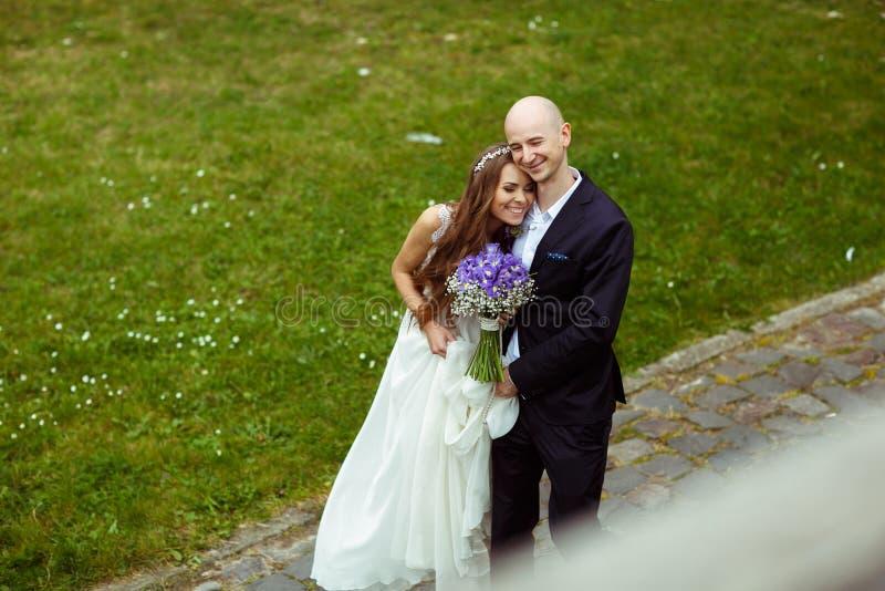 De gelukkige bruid leunt aan de bruidegom die op de weg koesteren stock afbeelding