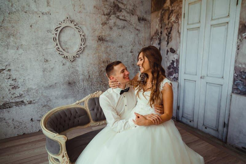 De gelukkige bruid met donker blonde lang haar zit op groom& x27; s knieën stock foto