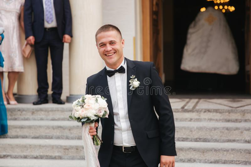 De gelukkige bruidegom wacht op de bruid door de kerk Wacht op eerste blik royalty-vrije stock foto