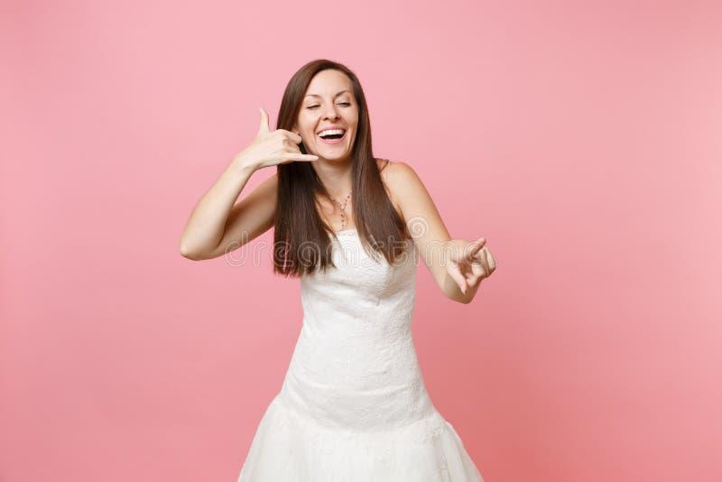 De gelukkige bruidvrouw in huwelijkskleding die telefoongebaar doen als zegt: roep me terug met hand en vingers als het spreken stock afbeeldingen