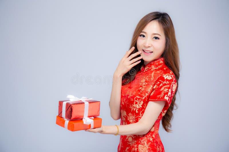 De gelukkige Chinese jonge Aziatische vrouw die van het Nieuwjaar mooie portret rode die giftdoos houden op witte achtergrond wor royalty-vrije stock foto