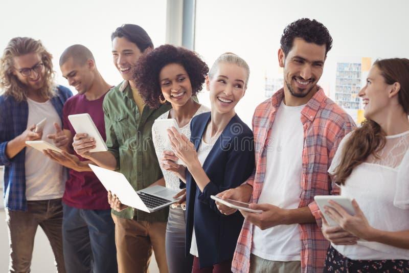 De gelukkige creatieve van de commerciële technologieën teamholding samen op kantoor stock foto