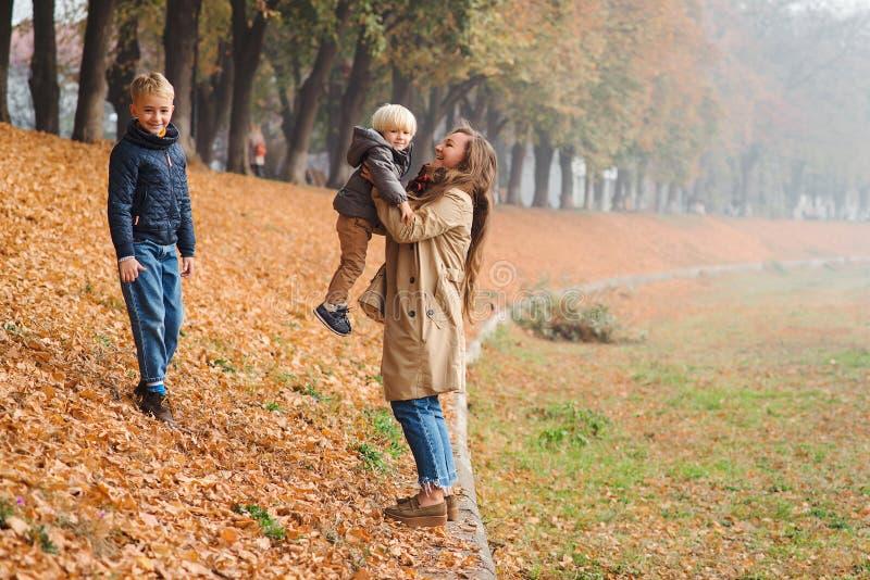 De gelukkige dag van de familie enjoing herfst Jonge moeder en kinderen op de herfstgang in park Leuke broers die pret met mamma  stock foto's