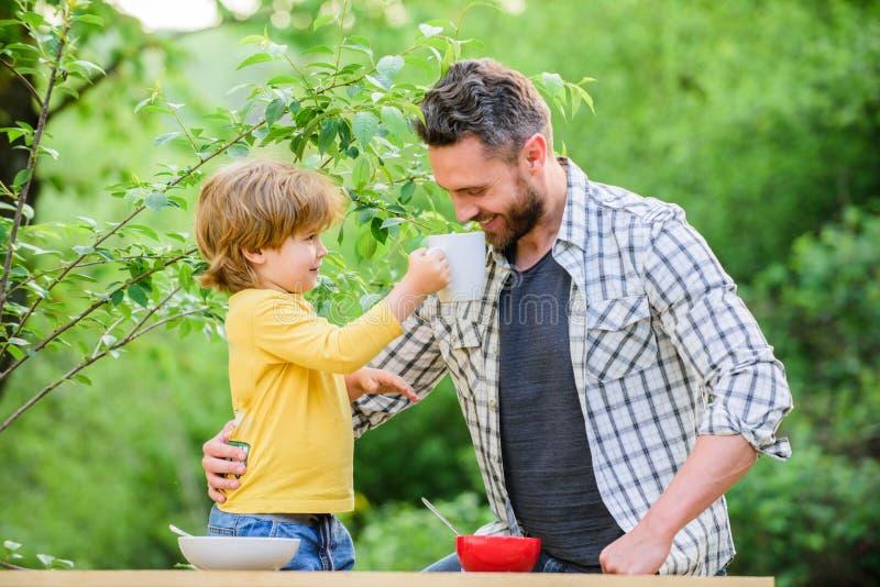 De gelukkige Dag van Vaders Weinig jongen met papa heeft ontbijtzoon en vader die melkhavermoutpap eten Kinderjarengeluk Baby royalty-vrije stock fotografie