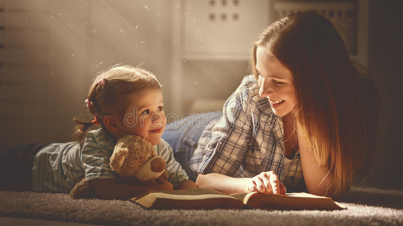De gelukkige de familiemoeder en dochter lezen een boek in avond stock foto's