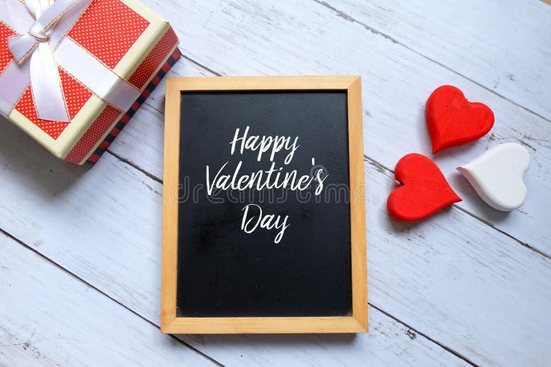 De gelukkige die dag van Valentine ` s op een bord met houten handrafthart en doos wordt geschreven royalty-vrije stock afbeelding