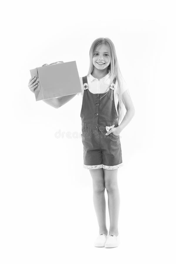 De gelukkige die papieren zak van de meisjesgreep op wit wordt geïsoleerd Weinig shopaholic glimlach met het winkelen zak Kindkla stock foto