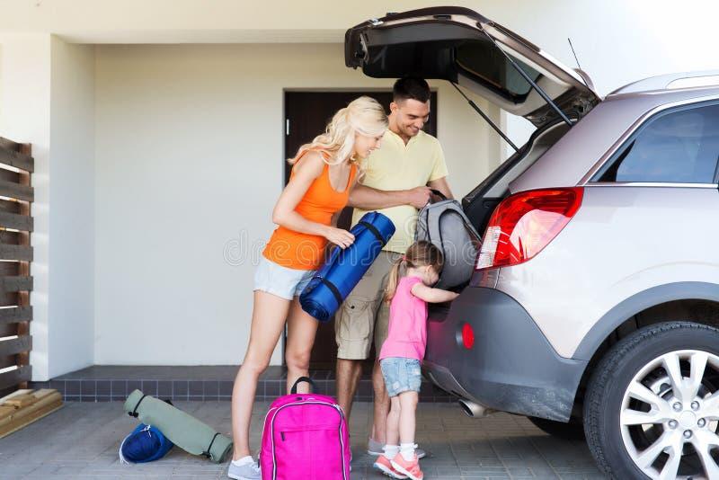 De gelukkige dingen van de familieverpakking aan auto die thuis parkeren stock foto