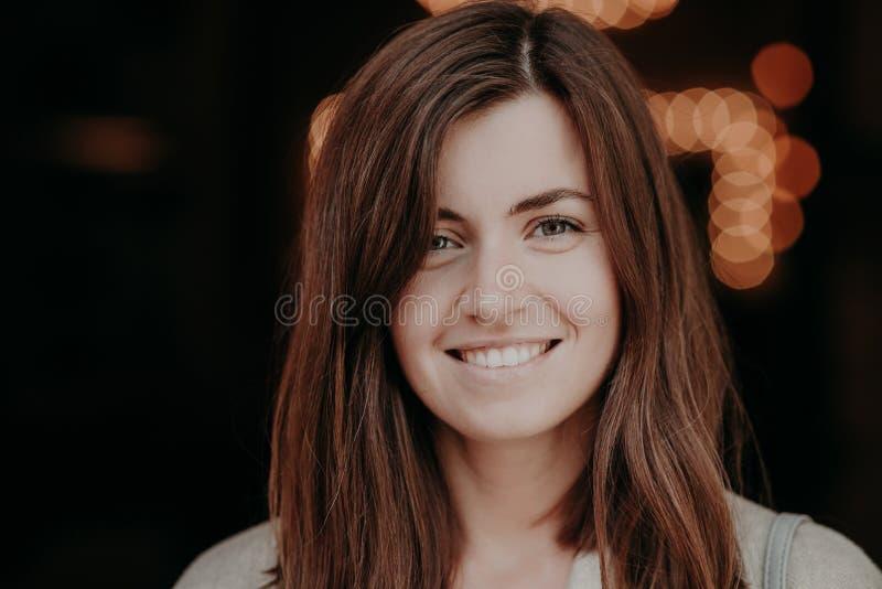 De gelukkige donkerbruine glimlachende vrouw met donker haar, witte tanden, bekijkt positief camera, toont haar natuurlijke schoo stock afbeelding