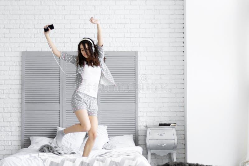 De gelukkige donkerbruine vrouw draagt grijze pyjama's Klok als koffiekop, krant en pen royalty-vrije stock fotografie