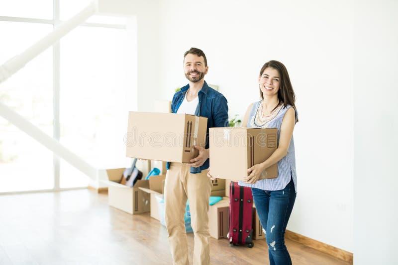 De gelukkige dozen van het paar dragende karton in nieuw huis royalty-vrije stock fotografie