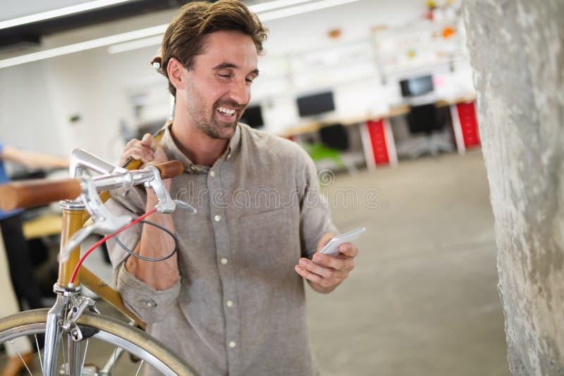 De gelukkige dragende fiets van de medewerkerzakenman in modern bureau royalty-vrije stock afbeeldingen