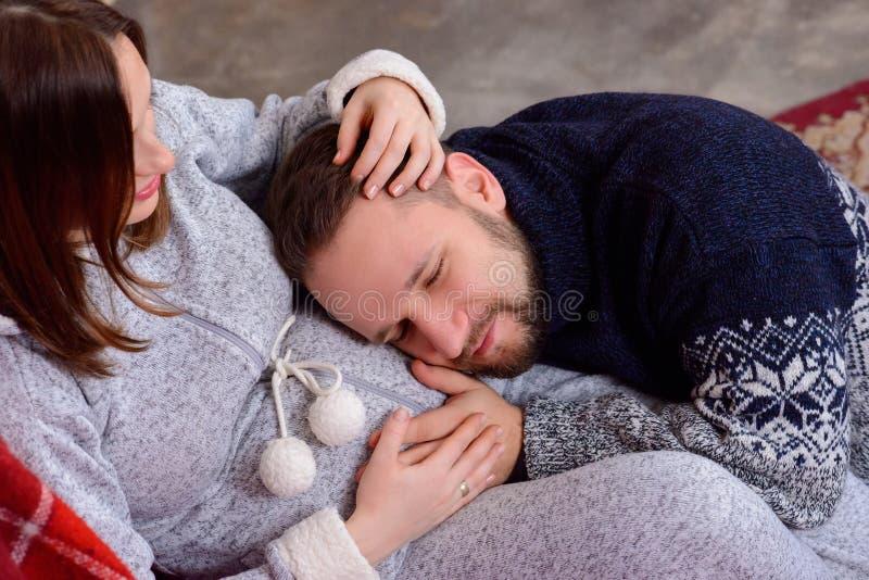 De gelukkige echtgenoot luistert aan babyhartslag die op buik van zijn zwangere vrouw liggen stock afbeelding