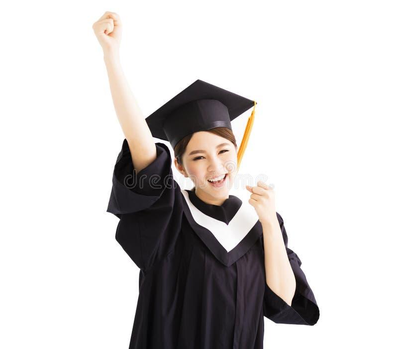De gelukkige een diploma behalende student heft hand met succesgebaar op stock afbeelding