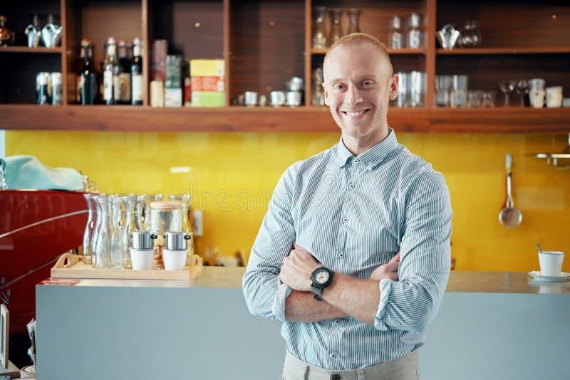 De gelukkige eigenaar die van de koffiewinkel bij camera glimlachen stock fotografie