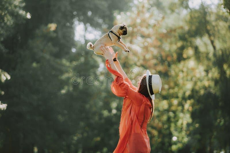 De gelukkige eigenaar werpt cheerfully op haar hond royalty-vrije stock foto's